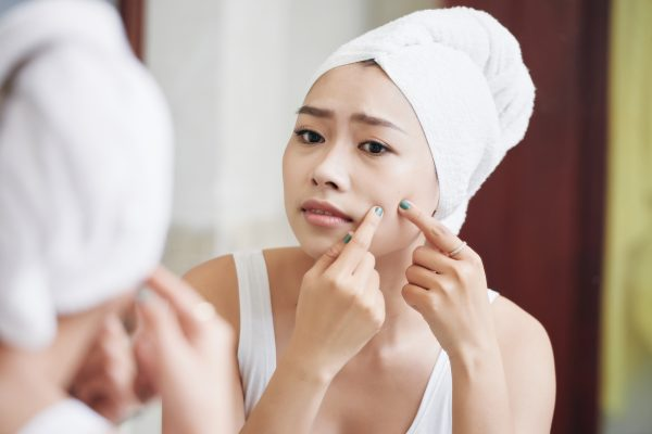 Young Asian woman in towel standing in front of mirror and popping pimples looking concerned