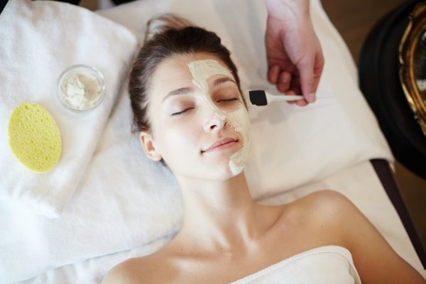 Top view portrait of beautiful young woman in SPA, lying on massage table with eyes closed while cosmetologist applying face mask to her face